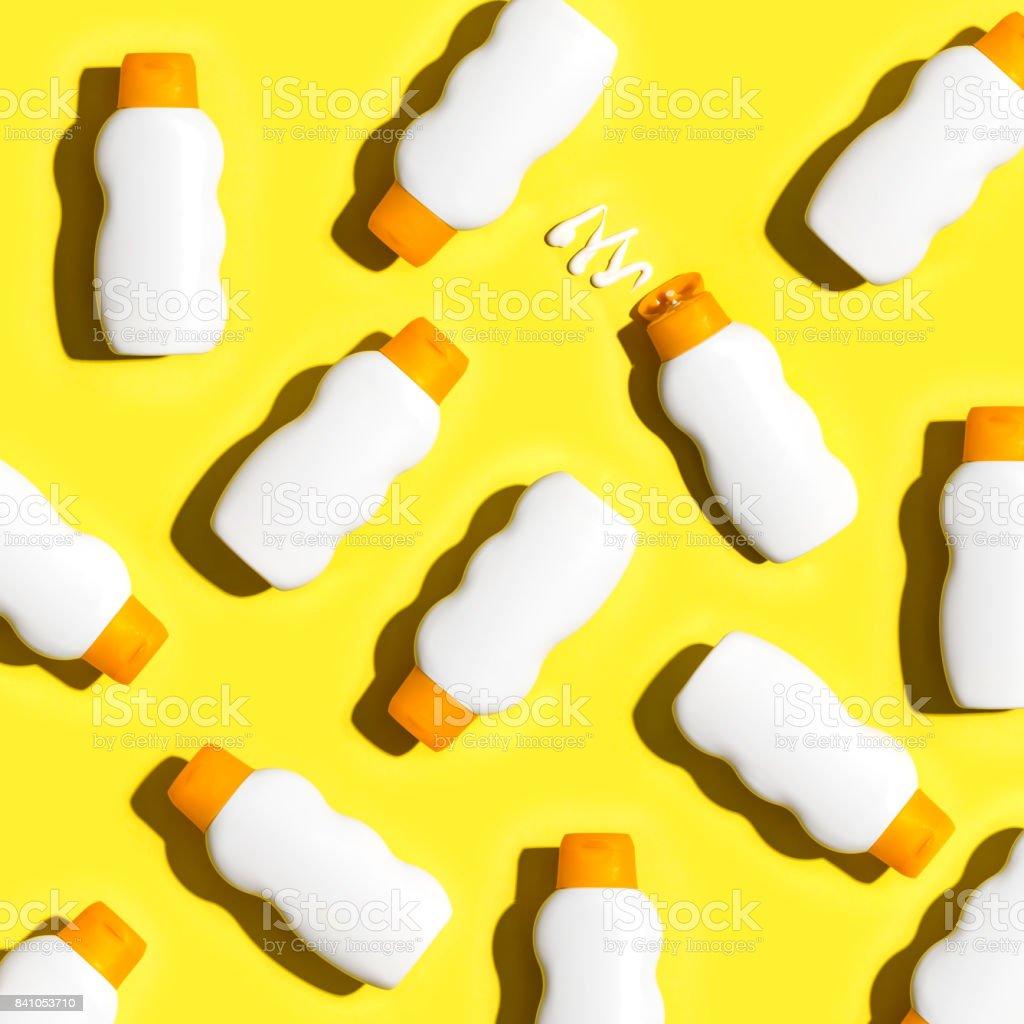 Bloqueador solar botellas de fondo amarillo - foto de stock