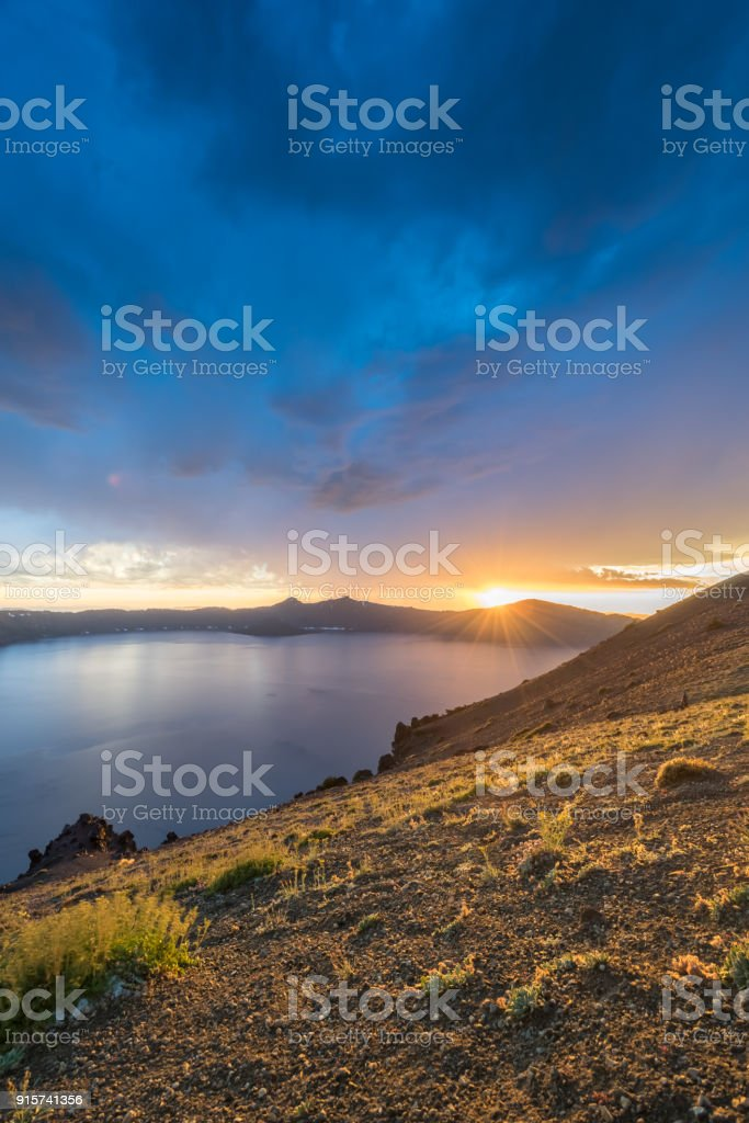 Sunbursts Over The Rim Of Crater Lake stock photo