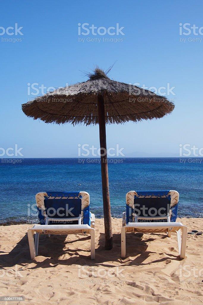 Sunchairs under an umbrella at tropical beach royalty-free stock photo