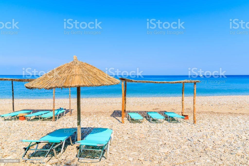 Sunchairs with umbrellas on Potami beach, Samos island, Greece stock photo