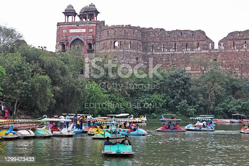 Delhi, India – March 15, 2015: Local people and tourists enjoying pedalo rides on a Sunday afternoon on the boating lake in the shadow of the 16th century Mughal fort of Purana Qila. The lake is a remnant of the moat that formerly surrounded the citadel