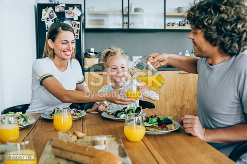 Photo of a young happy family having lunch or dinner together.