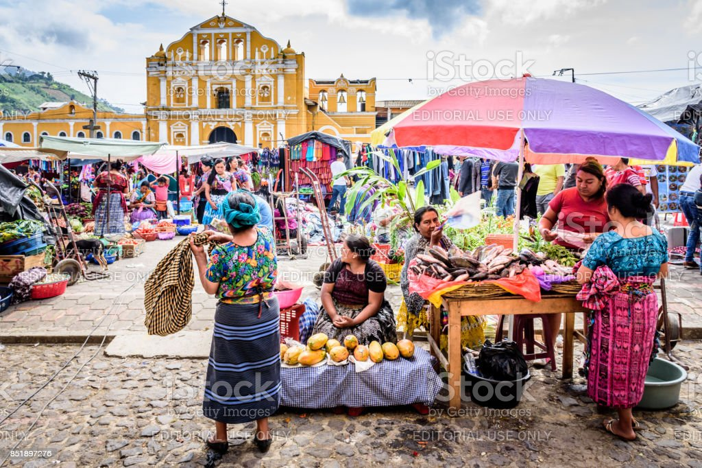 Sunday market in town plaza, Santa Maria de Jesus, Guatemala Santa Maria de Jesus, Guatemala - August 20, 2017: Colorful Sunday market in front of church in small indigenous town on slopes of Agua volcano near UNESCO World Heritage Site of Antigua. Adult Stock Photo