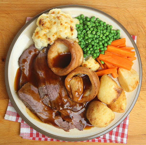 sunday roast beef dinner with yorkshire pudding, vegetables - gebraden vlees stockfoto's en -beelden