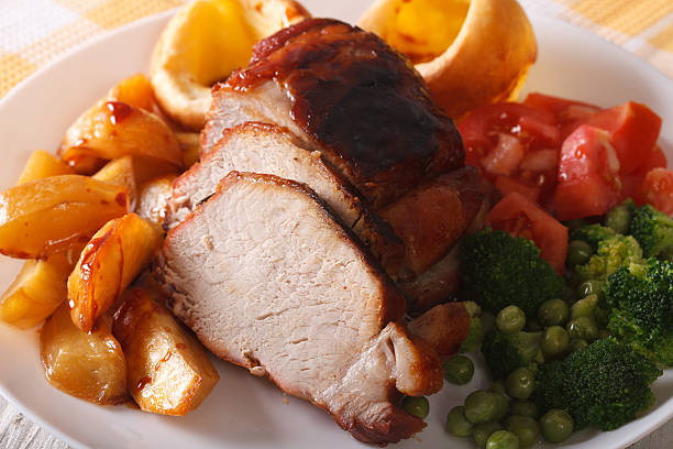 sunday roast: pork with vegetables and yorkshire pudding - tranchieren stock-fotos und bilder