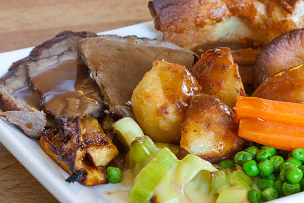 a sunday roast with pork, potatoes, carrots and peas - gebraden vlees stockfoto's en -beelden