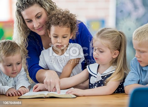 A Sunday school teacher guides a diverse group of young children in reading the bible, at a table indoors.