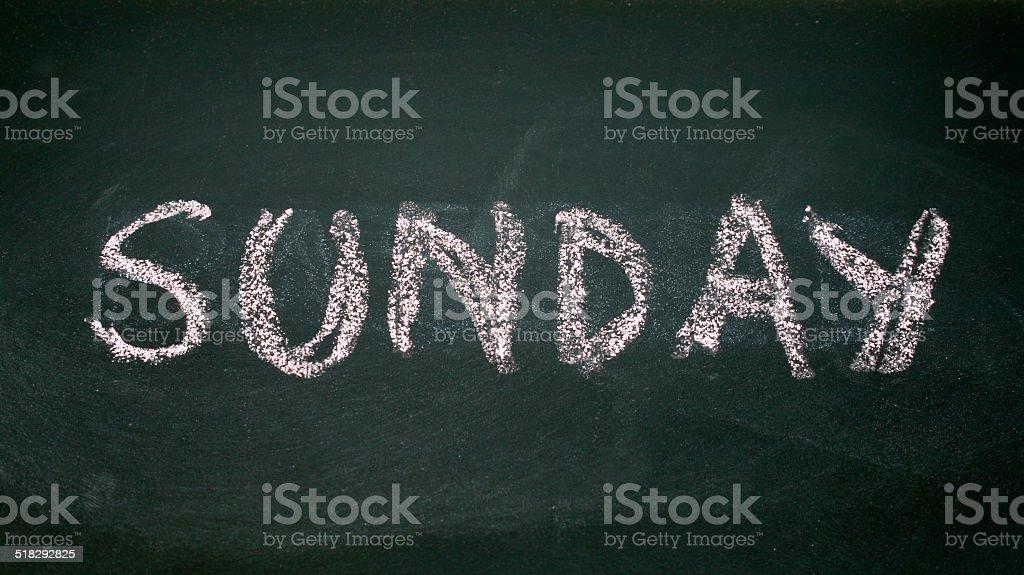 sunday written with chalk on blackboard stock photo