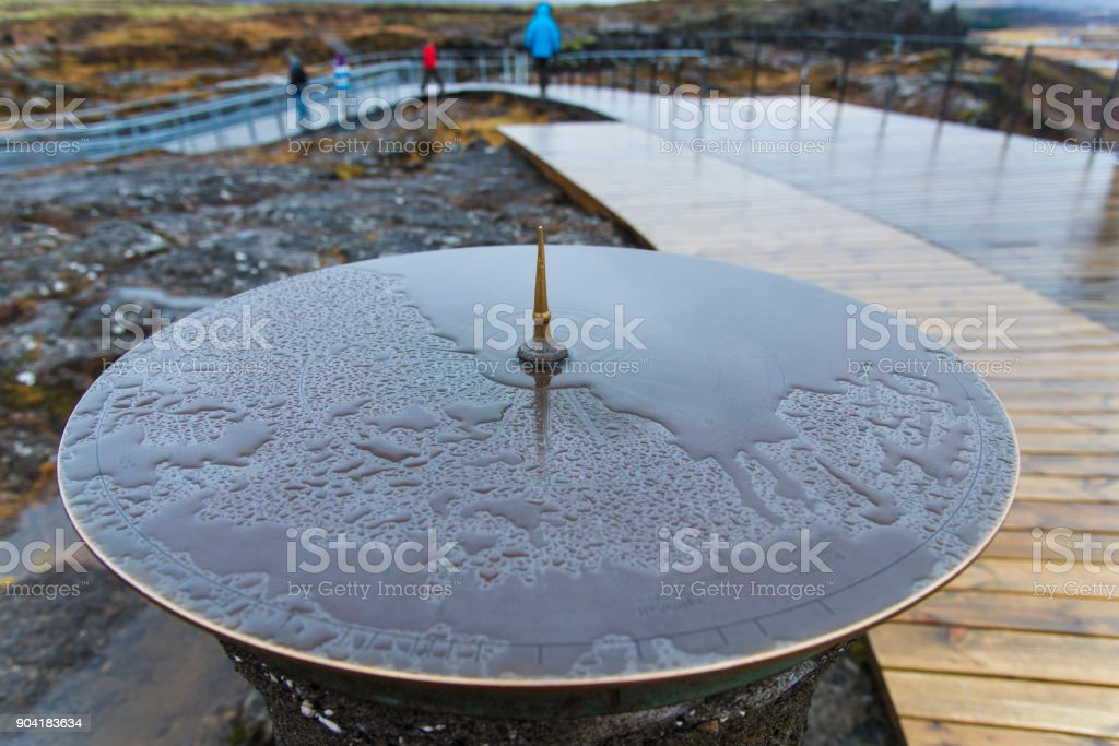 Sundial in Thingvellir National Park in winter after raining, with some tourists on the way ,Iceland. stock photo