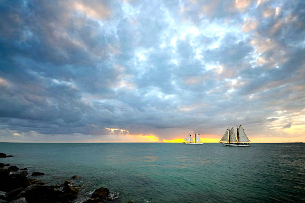 """Sundown Schooners in Key West Beautiful, """"postcard-quality"""" scene of schooners against the setting sun to the west taken from the beach jetty at Fort Zachery Taylor park in Key West, Florida, the beach/sunset corner in December. mike cherim stock pictures, royalty-free photos & images"""