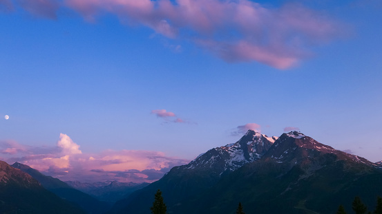 Beautiful pink sky with clouds in alpine landscape.