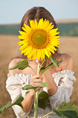 Close-up of a young woman holding a sunflower in front of her face