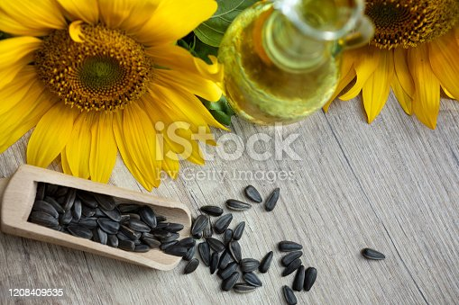 Little glass bottle with sunflower oil with seeds and sunflower on wooden table, top view