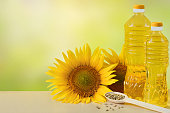 Sunflower oil in bottles, seeds and flowers of sunflower close up with copy space for text