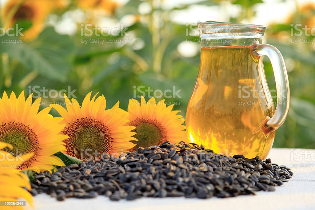 Sunflower oil Sunflower oil with sunflowers and sunflower seeds in sunflower field. Shallow DOF. Agricultural Field Stock Photo