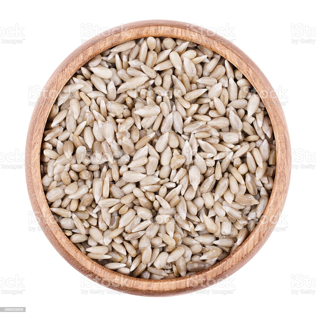 Sunflower seeds in a bowl on white background stock photo