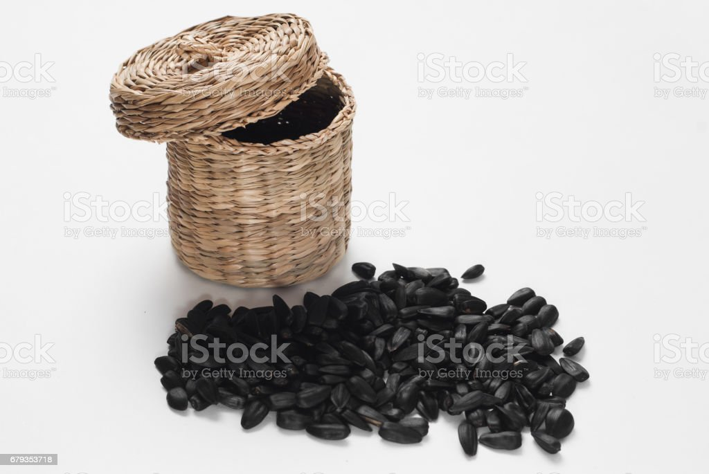 sunflower seeds in a wicker basket with lid on white background, royalty-free stock photo