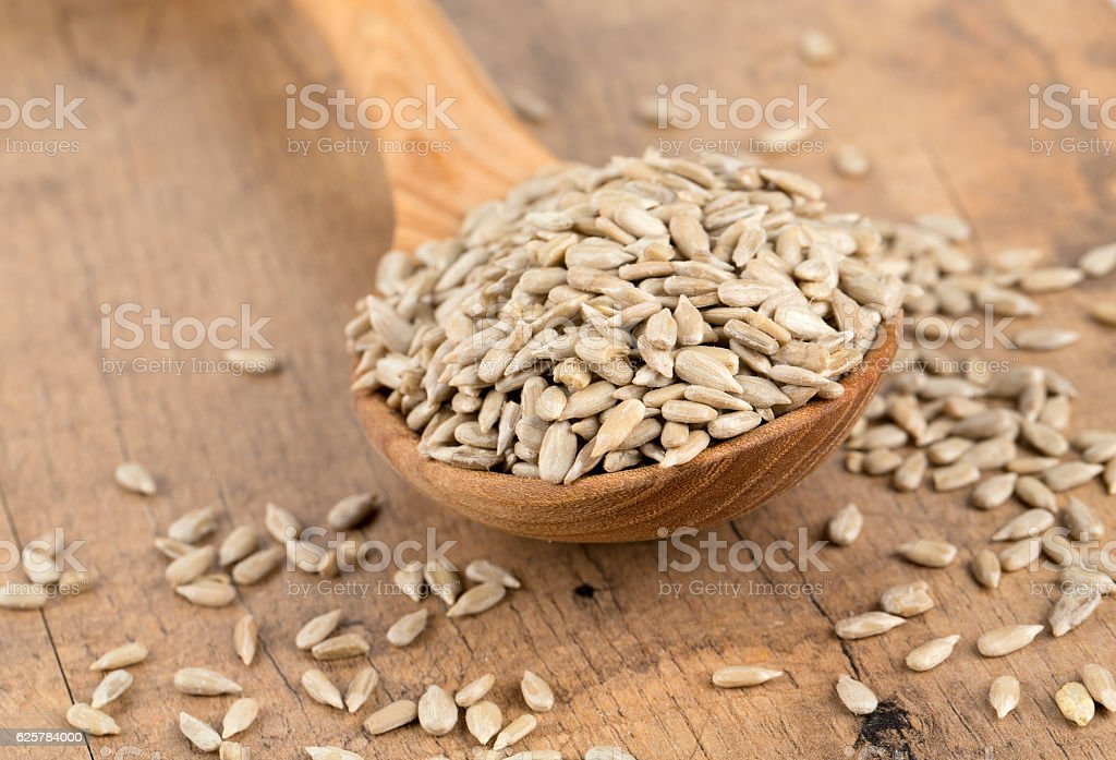 sunflower seeds in a wooden spoon stock photo