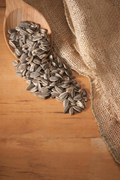 Sunflower Seeds Wooden Spoon Vertical Overhead stock photo