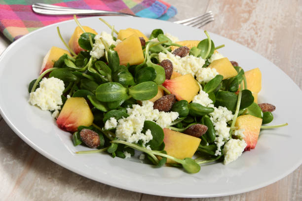 Sunflower Sprout Salad with Peaches, Cheese, and Almonds stock photo