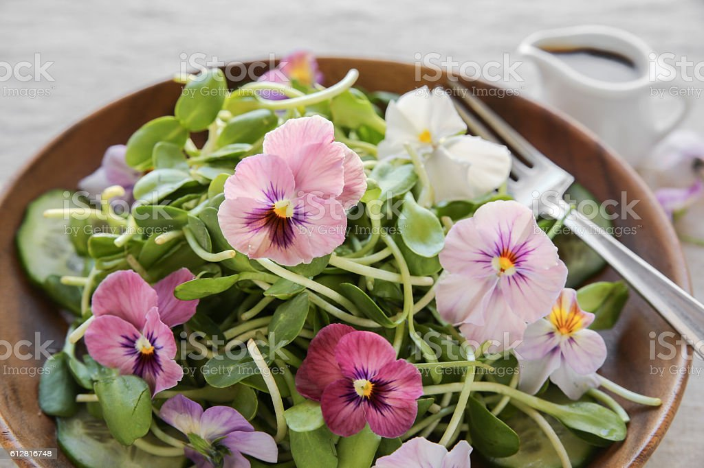 Sunflower sprouts, cucumber and edible flowers salad on wooden b stock photo