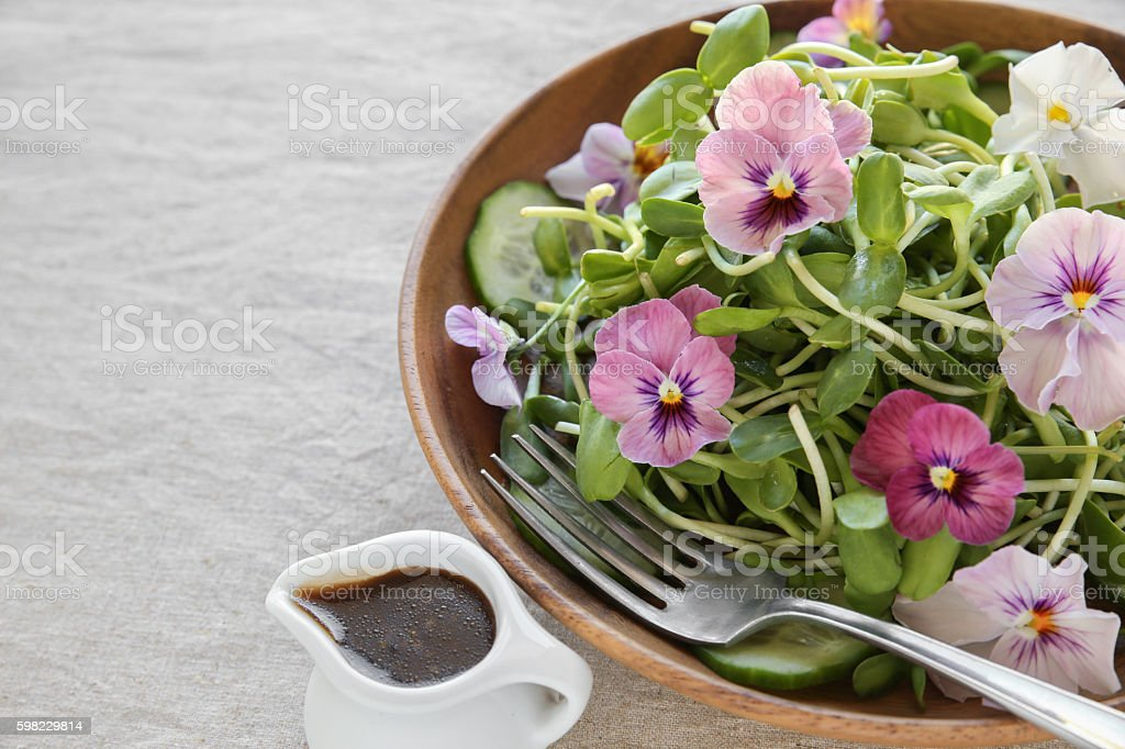 Sunflower sprouts, cucumber and edible flowers salad on wooden bowl foto royalty-free
