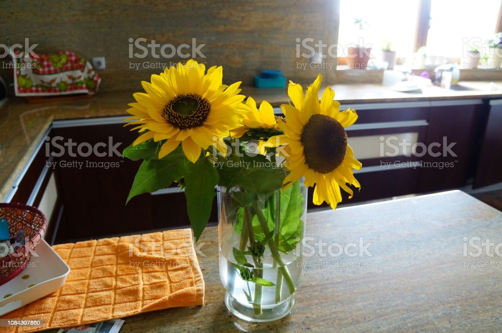 Sunflowers in a vase filled with water on top of a kitchen balcony