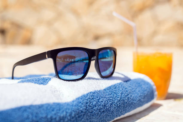 Sunglass on a towel with a drink stock photo