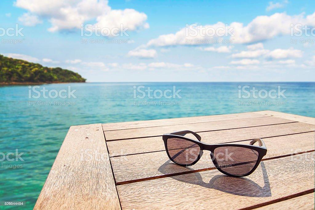 sunglass on wood terrace at seaside with nice blue sky stock photo