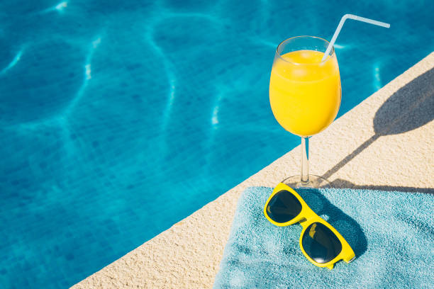 Sunglasses and a glass of orange juice in the resort hotel Sunglasses and a glass of orange juice in the resort hotel poolside stock pictures, royalty-free photos & images