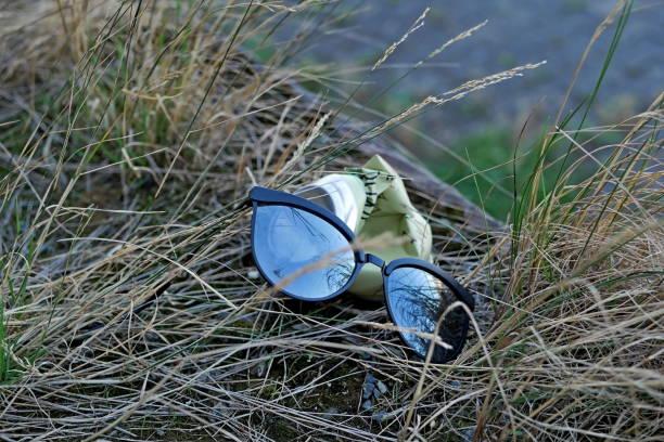 Sonnenbrille und einem alten können in den Rasen - Umgebung Müll – Foto