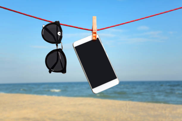 Sunglasses and mobile phone on summer vacation background stock photo