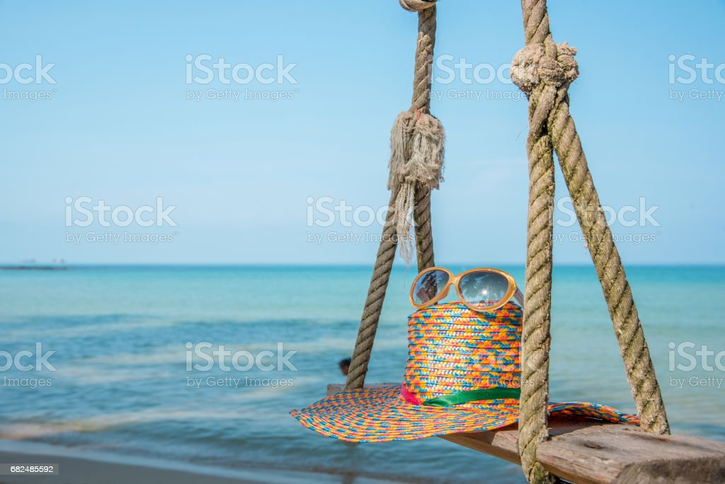 sunglasses and straw hat with blur blue sea and sky background Стоковые фото Стоковая фотография