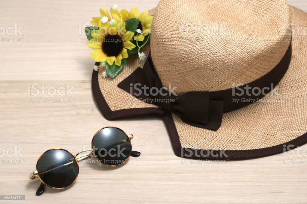 Sunglasses and straw hat with sunflowers on wood. stock photo