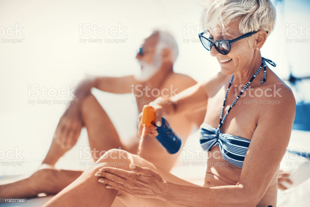 Sunglasses and sunscreen are good enough for my protection. Senior woman applying sunscreen on her leg at the yacht cruse. Active Seniors Stock Photo
