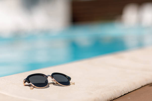 sunglasses by the pool on a sunny summer day. sunglasses by the pool on a sunny summer day. summer background. poolside stock pictures, royalty-free photos & images