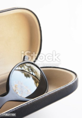 Designer sunglasses in fashionable black with outdoor reflection in lens inside open case against white backdrop.