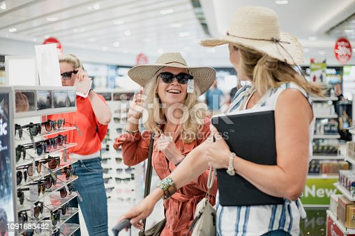 Mature woman are being playful while trying on sunglasses in Duty Free at the airport.