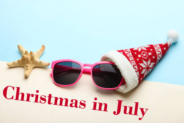sunglasses in a christmas cap - july stock photos and pictures