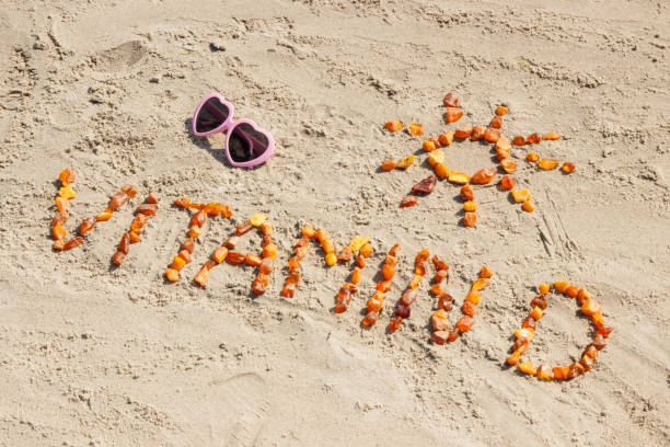 sunglasses, inscription vitamin d and shape of sun on sand at beach, summer time and healthy lifestyle concept - vitamin d zdjęcia i obrazy z banku zdjęć