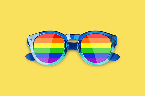 Sunglasses LGBTQ community flag colors yellow background close up, rainbow pattern glasses, LGBT pride people symbol, gay, lesbian etc love sign, human diversity concept, summer holidays fun accessory