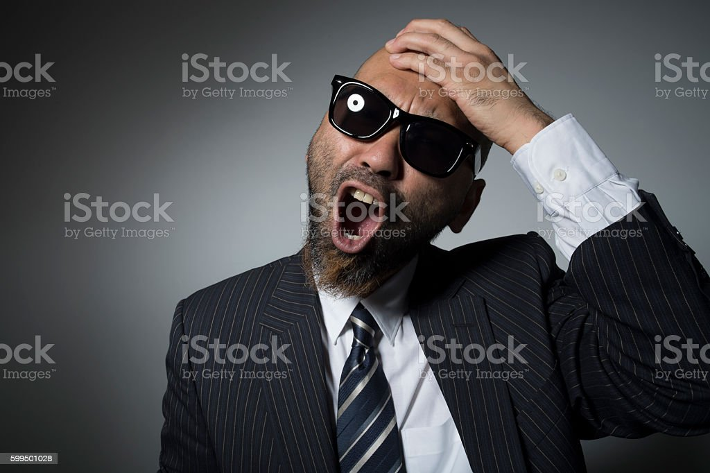 Sunglasses man put a hand to his head. stock photo