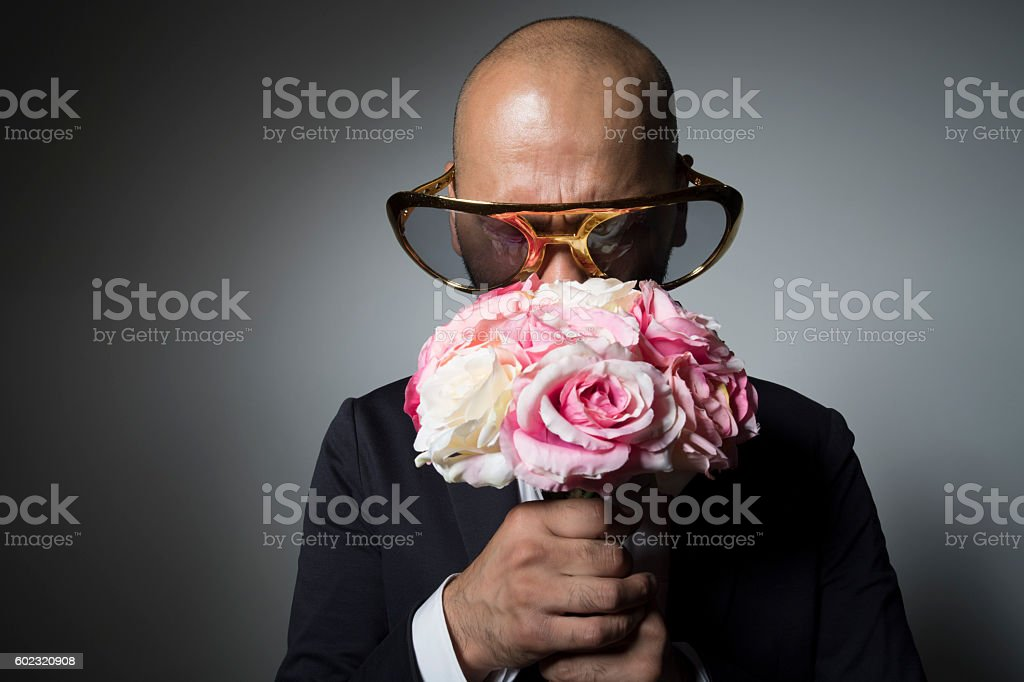 Sunglasses man with a bouquet of flowers is pointing down. stock photo
