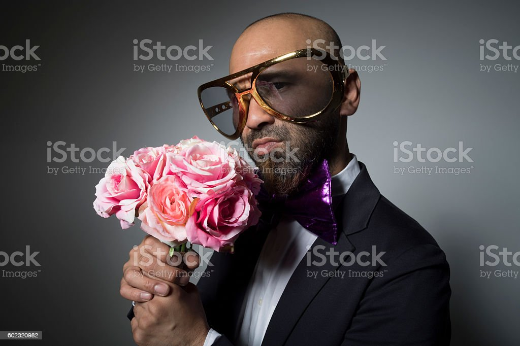 Sunglasses man with a bouquet of flowers looking at me. stock photo