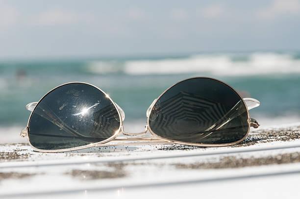 sonnenbrille auf liegestuhl und sand - sonnenbrand heilen stock-fotos und bilder