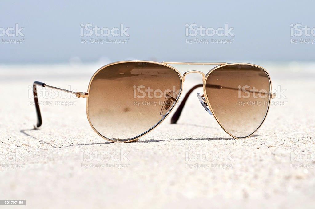Sunglasses on a sand beach stock photo