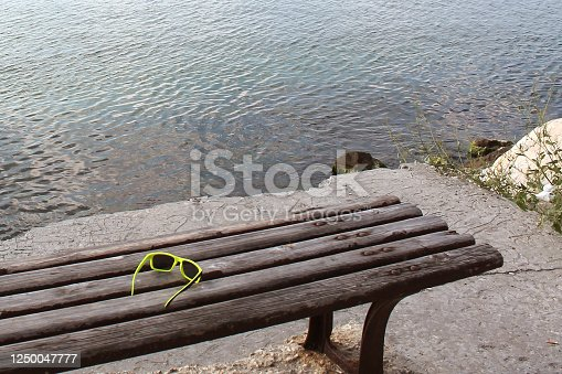 sunglasses on an empty bench near the sea