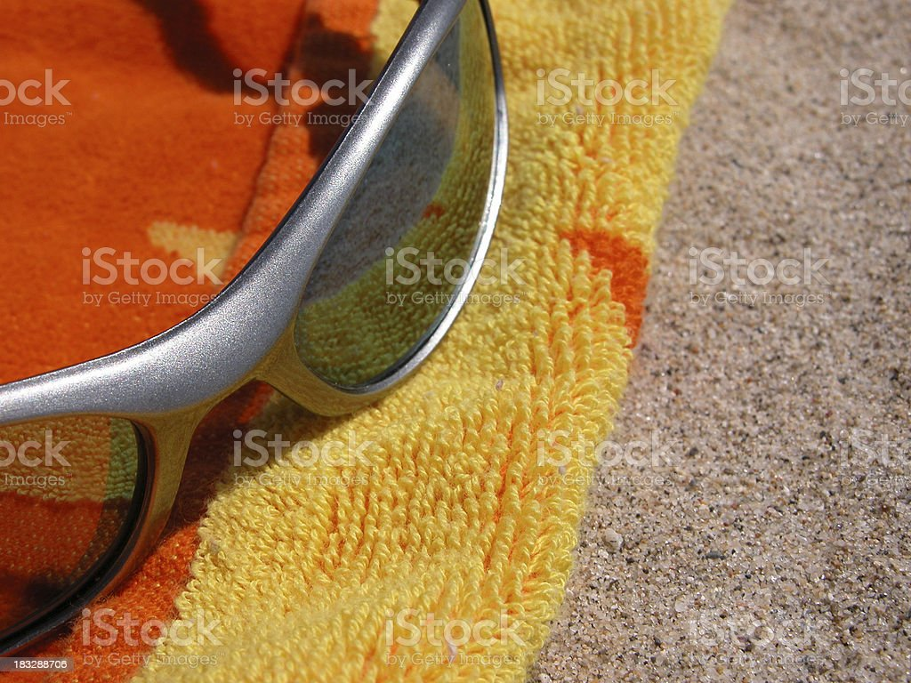\'close up of sunglasses sitting on colorful beach towel in Santa...