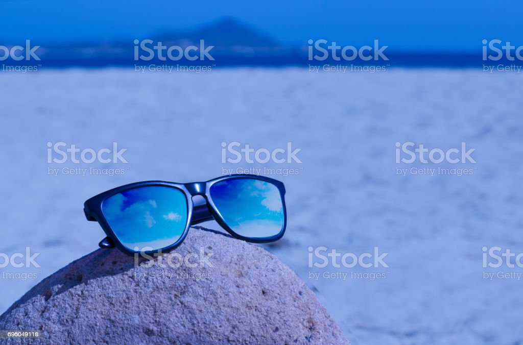 Sunglasses on rock in the beach stock photo