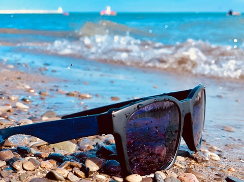 854222674 istock photo Sunglasses on the beach photograhy 1146537439
